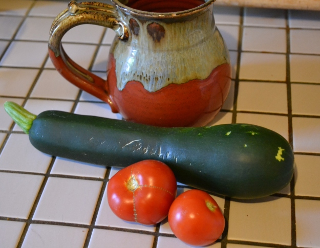first zucchini from a container and a few of the determinate tomatoes